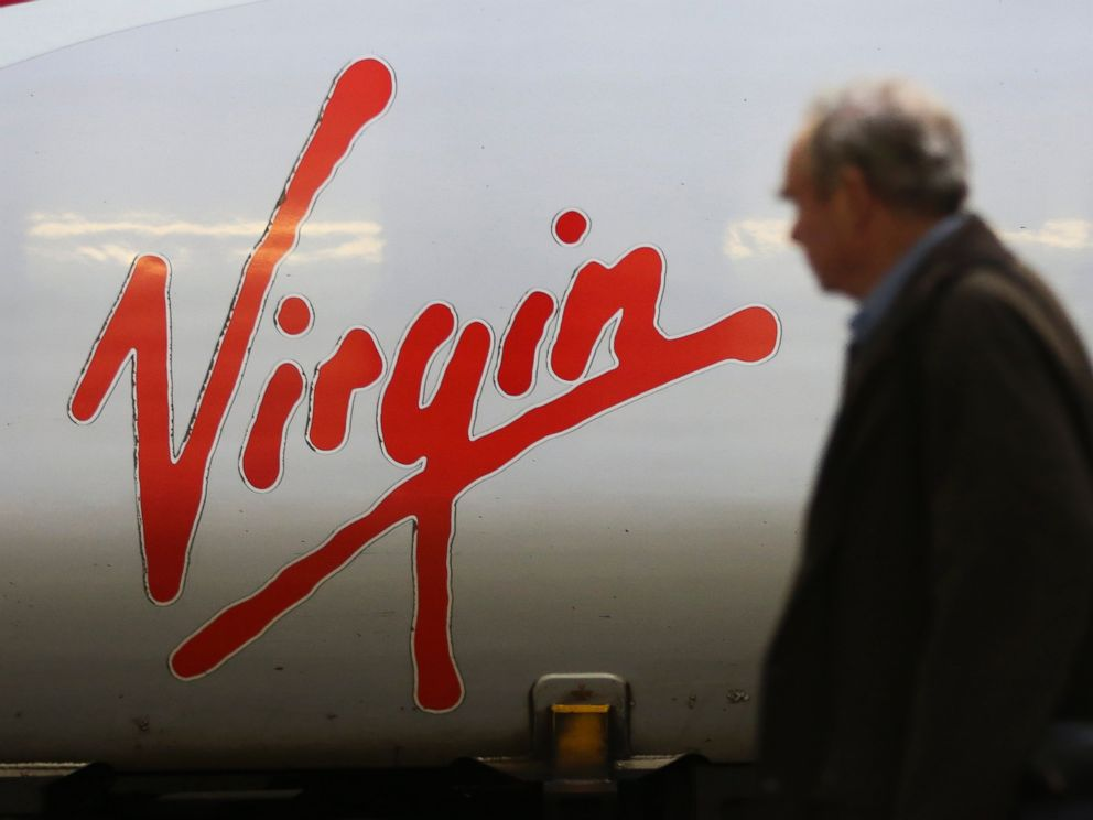 PHOTO: The Virgin logo sits on the side of a West Coast train, operated by Virgin Trains, as it stands beside a platform at Euston railway station in London, Nov. 27, 2014.