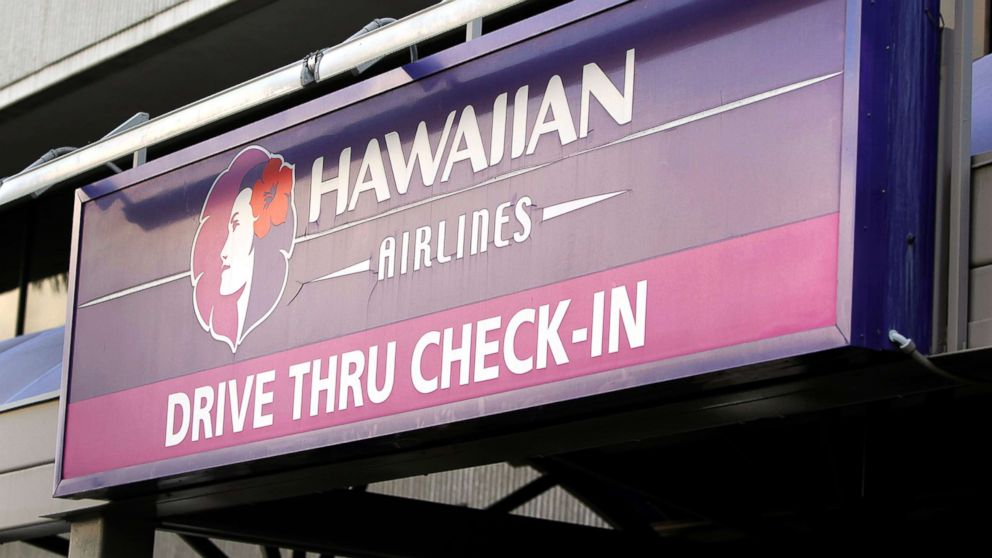 A sign directing travelers to drive thru check-in at Hawaiian Airlines Inc. is displayed at an airport in Honolulu, Hawaii, Jan. 9, 2013.