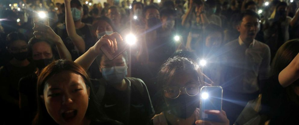 PHOTO: People hold up their phones at a memorial site for a teenage female protester, whom protesters claim was killed by police, at Sheung Shui district in Hong Kong, Oct. 11, 2019.