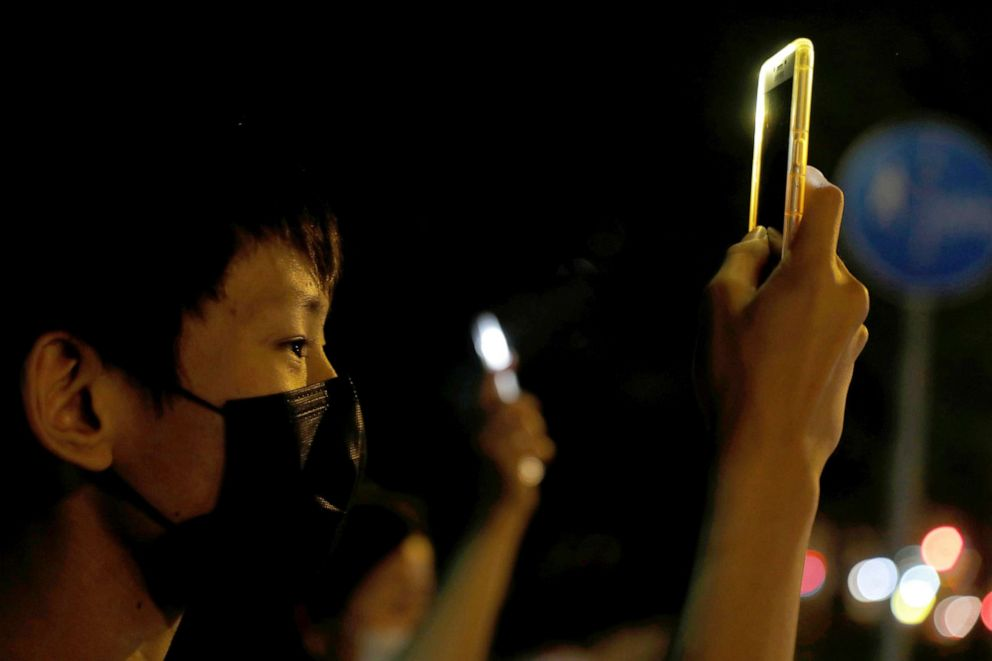 PHOTO: A man holds up his phone as people form a human chain during a protest in Tai Po, Hong Kong, Oct. 11, 2019.