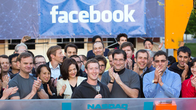 PHOTO: Mark Zuckerberg, chief executive officer of Facebook Inc., center, Sheryl Sandberg, chief operating officer of Facebook, center left, and Robert Greifeld, chief executive officer of Nasdaq OMX Group Inc., center right, ring the opening bell for tra