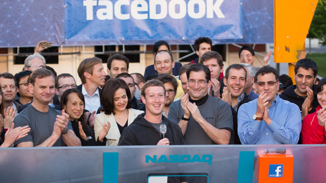 PHOTO: Mark Zuckerberg, CEO and founder of Facebook, and COO Sheryl Sandberg gather with a throng of cheering employees at the company headquarters in Menlo Park, Calif. to ring the stock markets opening bell, May 18, 2012.