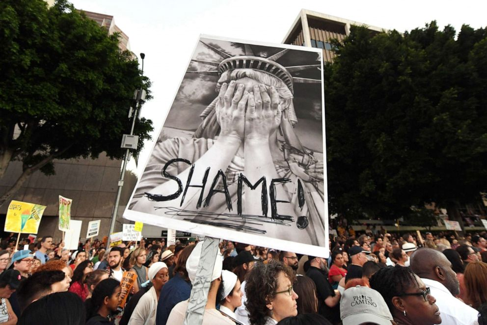 PHOTO: People protest against the upcoming ICE raids and detentions of refugee asylum seekers at a vigil outside the main ICE detention center (background) in downtown Los Angeles, July 12, 2019.