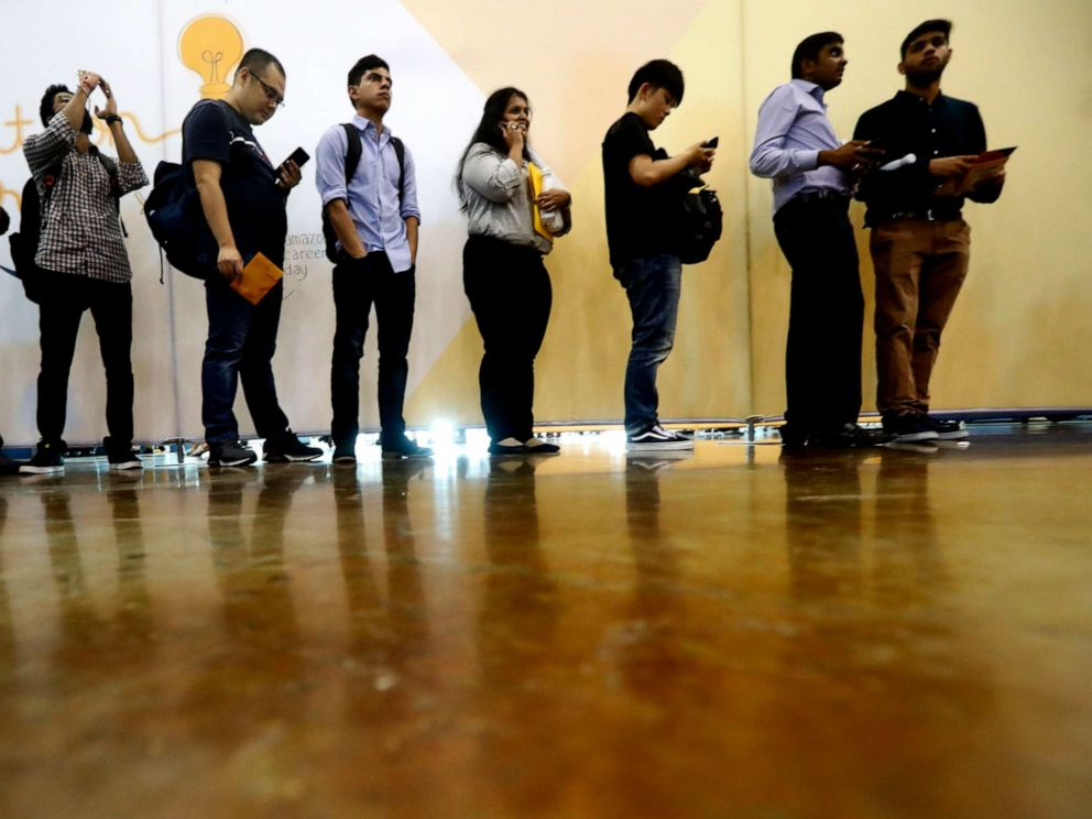 PHOTO: In this Sept. 17, 2019, photo job seekers line up to speak to recruiters during an Amazon job fair in Dallas.