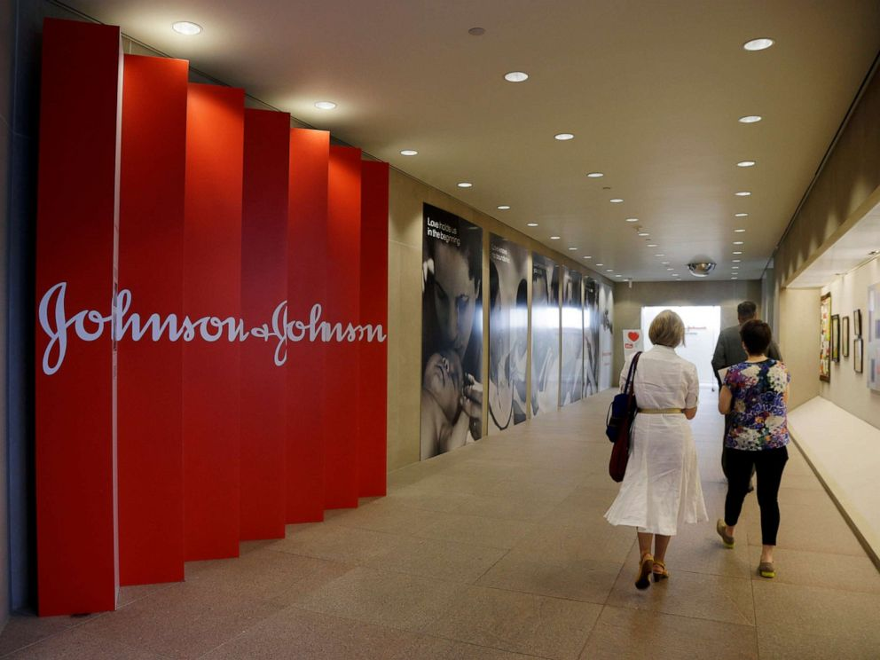 PHOTO: People walk along a corridor at the headquarters of Johnson & Johnson in New Brunswick, N.J., July 30, 2013.