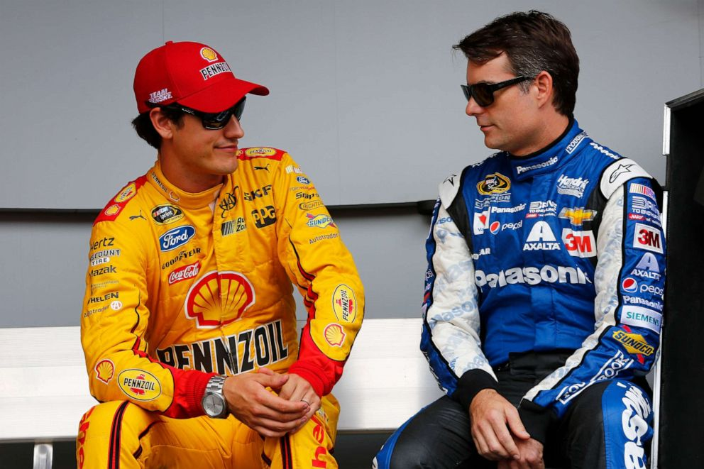 PHOTO: Joey Logano, driver of the #22 Shell-Pennzoil Ford, and Jeff Gordon, driver of the #24 PANASONIC Chevrolet, talk backstage at the driver introductions prior to the NASCAR Sprint Cup Series Quicken Loans 400, June 14, 2015. in Brooklyn, Mich.