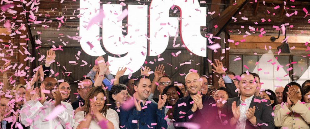 PHOTO: Lyft co-founders John Zimmer, front third from left, and Logan Green, front third from right, cheer as they as they ring a ceremonial opening bell in Los Angeles, March 29, 2019.