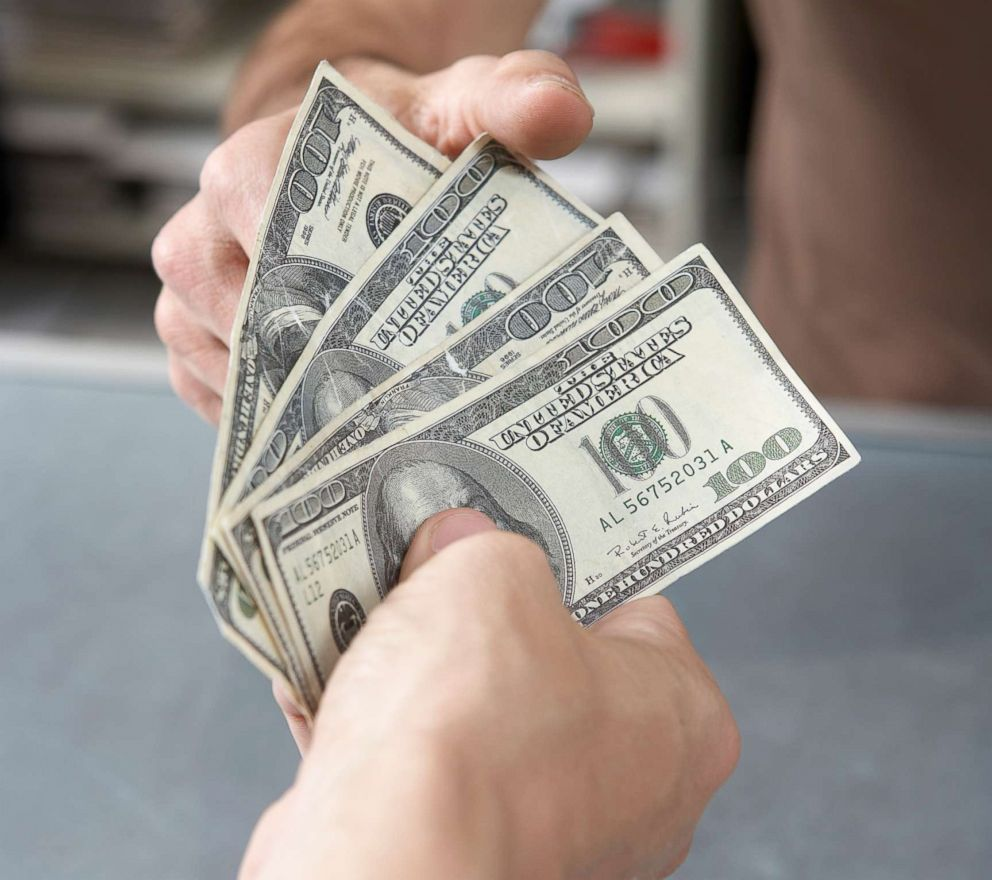 PHOTO: A man hands cash to another person in an undated stock photo.