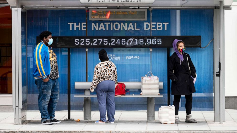 PHOTO: Passengers wearing face masks wait for their bus in front of a national debt display on Pennsylvania Ave. NW in Washington, May 18, 2020.