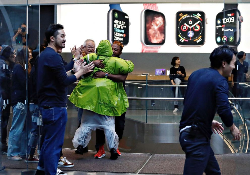 PHOTO: Apple Store staff person greets customers who have been waiting in line to purchase Apples new iPhone XS and XS Max in Tokyos Omotesando shopping district, Sept. 21, 2018.