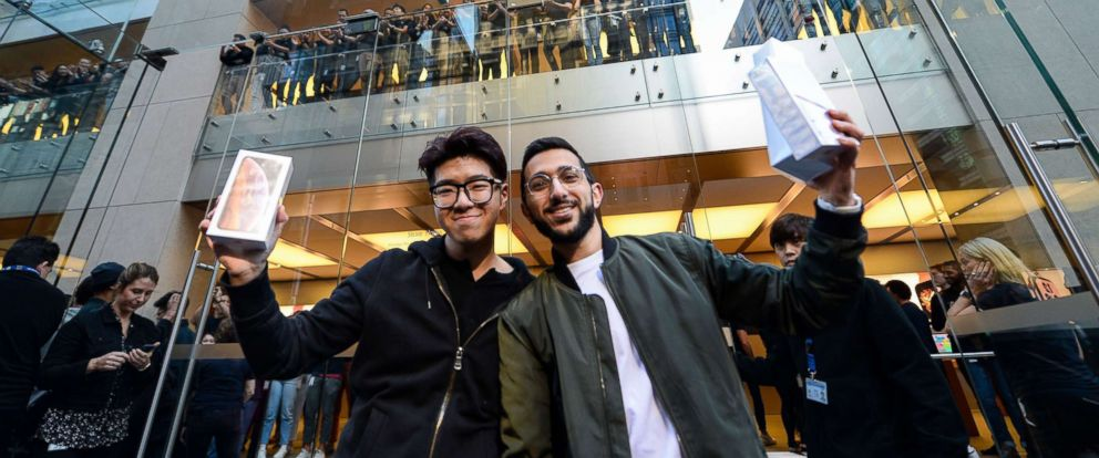 PHOTO: Sydney student Teddy Lee, left, and Mazen Kourouche hold up their new iPhones after being the first customers in line for new products at the Apple Store in Sydney, Sept. 2018.
