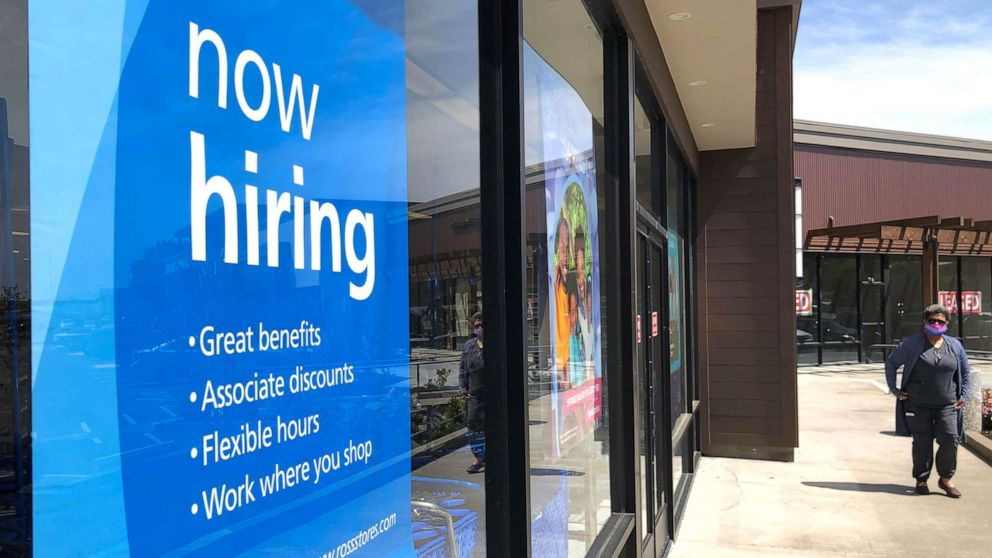 PHOTO: In this April 2, 2021, file photo, a pedestrian walks by a now hiring sign at a store in San Rafael, Calif.
