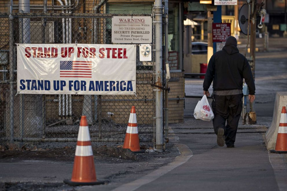 PHOTO: A man walks past a Stand Up For Steel, Stand Up For America sign while arriving at the U.S. Steel Corp. Clairton Plant coke manufacturing facility in Clairton, Pa., March 11, 2018.