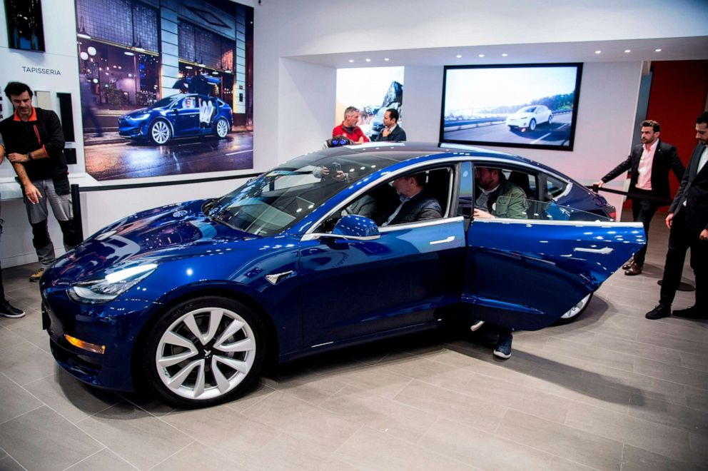 PHOTO: People check out a Tesla Model 3 during its first exhibition day in Spain, at the Teslas store in Barcelona on Nov. 14, 2018.
