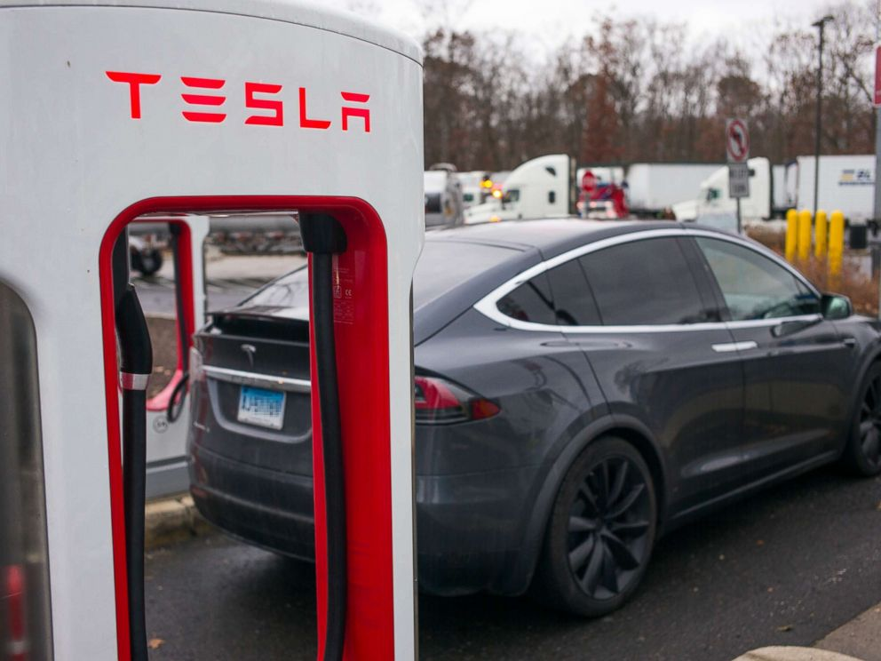 PHOTO: A Tesla X electric automobile recharges at a public charging station along Interstate 95 in Darien, Conn., Dec. 5, 2017.