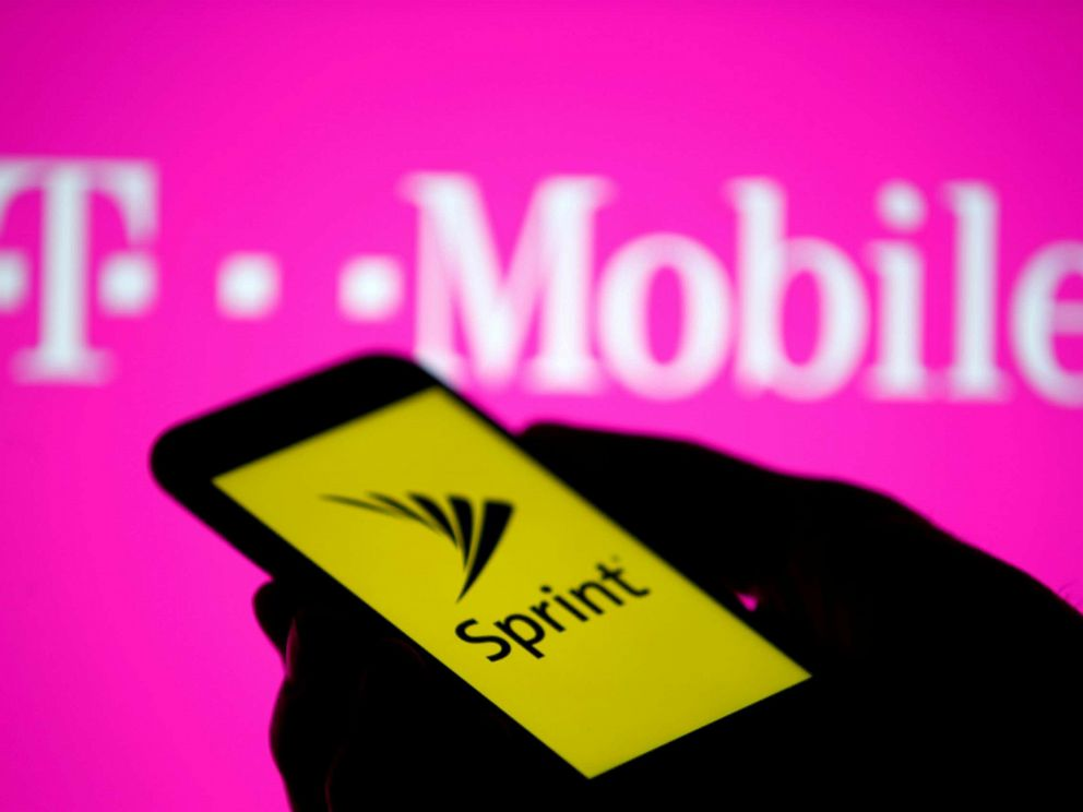 PHOTO: A posed photo shows a smartphone with Sprint logo in front of a screen projection of T-mobile logo.