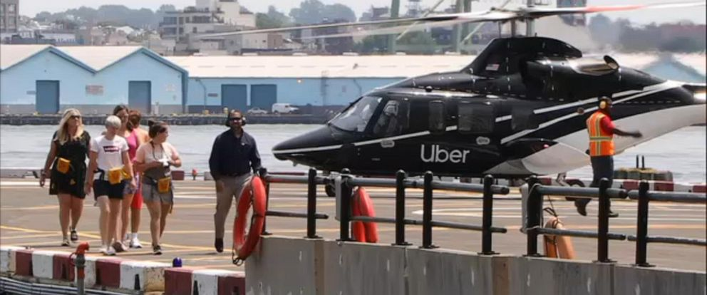 PHOTO: A group of people walk away from an Uber Air helicopter in New York on July 9, 2019.