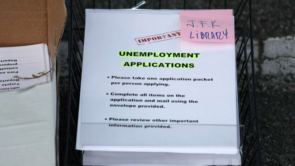 Unemployment applications are seen as City of Hialeah employees hand them out to people in front of the John F. Kennedy Library, April 8, 2020, in Hialeah, Fla.
