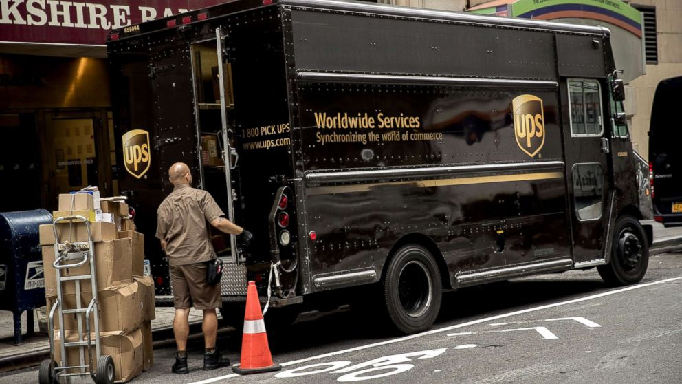 A driver for an independent contractor to United Parcel Service Inc. (UPS) prepares to load packages onto a delivery truck on a street in New York, July 24, 2017.