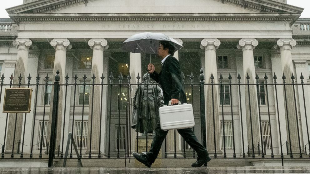 In this Thursday, Oct. 10, 2013 photo, a pedestrian walks past the U.S. Treasury Building in Washington on a rainy day.