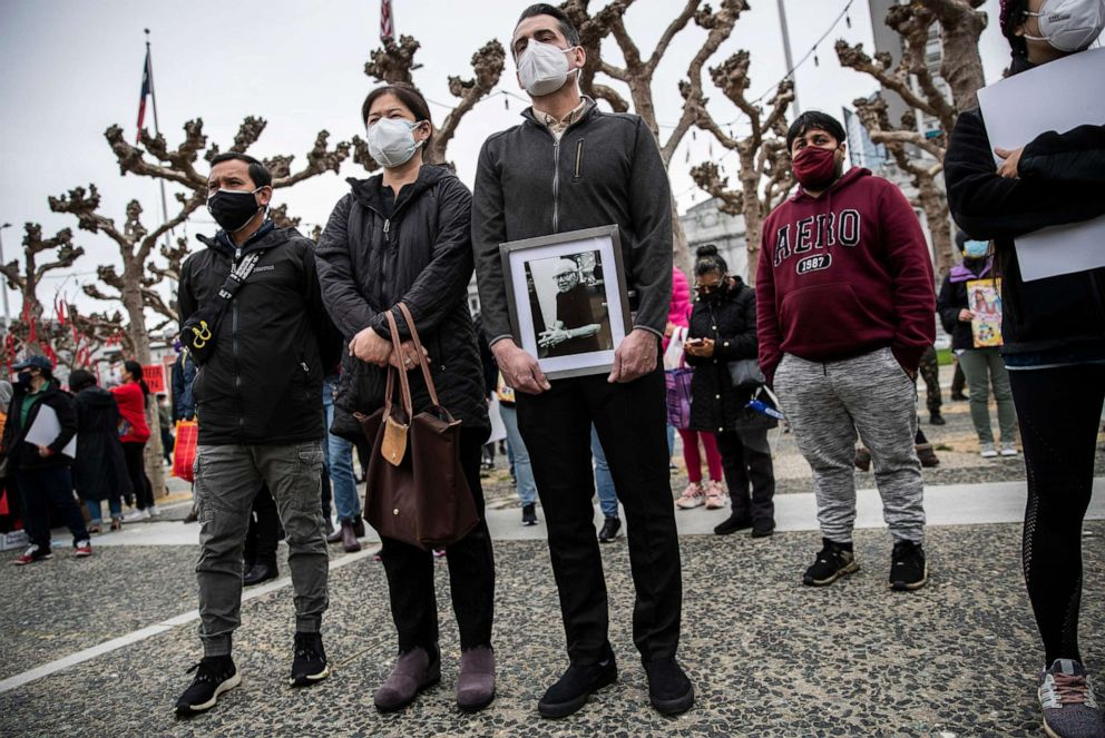 """PHOTO: Sanan Wannachit, Monthanus Ratanapakdee, and husband Eric Lawson, who holds a photograph of his late father-in-law Vicha Ratanapakdee, attend a """"Love our People: Heal our Communities"""" rally in San Francisco, Feb. 14, 2021."""