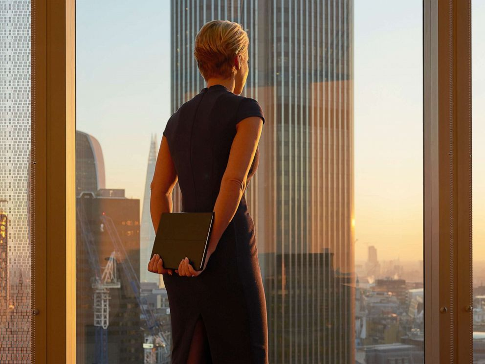 PHOTO: Woman in office standing at window.