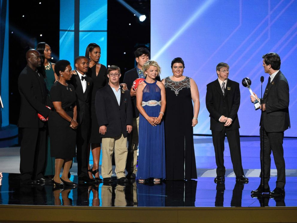 PHOTO: Timothy Shriver addresses former first lady Michelle Obama, fifth from left, and Special Olympic athletes as he accepts the Arthur Ashe Courage Award on behalf of his late mother at the Microsoft Theater, July 12, 2017, in Los Angeles.