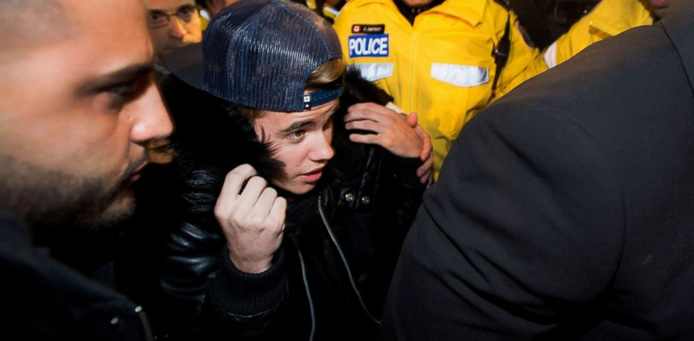 PHOTO:Justin Bieber is swarmed by media and police officers as he enters a police station in Toronto, Jan. 29, 2014.