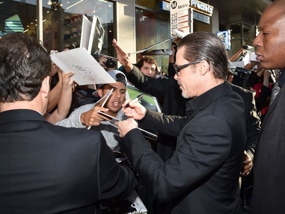 PHOTO: Brad Pitt signs autographs at the world premiere of Maleficent at the El Capitan Theatre, May 28, 2014 in Los Angeles.