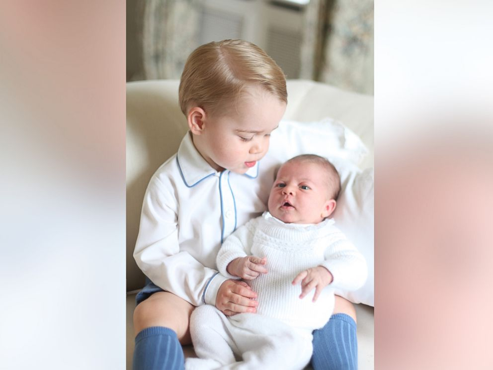 Photo britains princess charlotte right being held by her brother 2