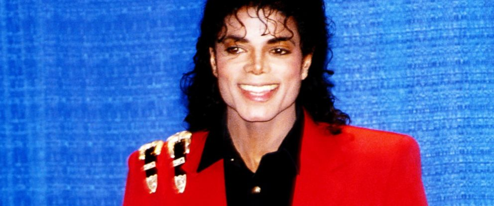PHOTO: Pop singer Michael Jackson poses for a portrait wearing a red sports coat with belt buckles on his right shoulder and a black arm band in 1988.