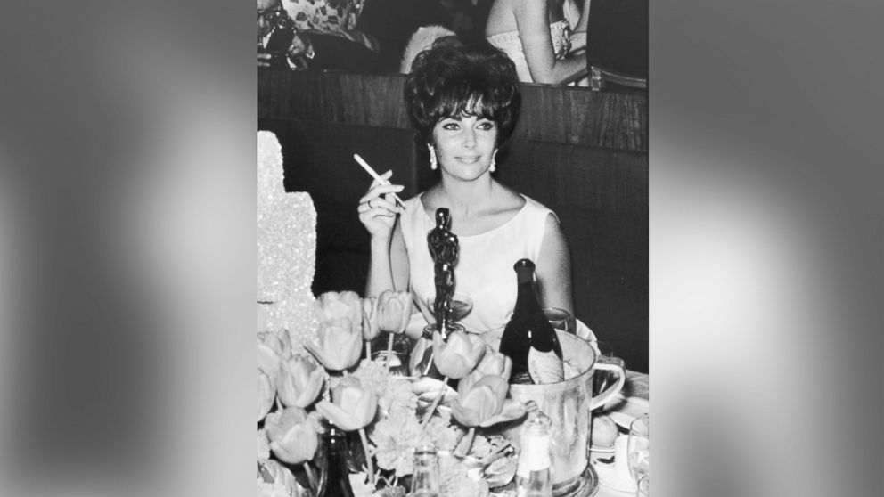 Elizabeth Taylor is pictured at a party in Hollywood, California, after winning an Oscar award, which is on table in front of her, circa 1961.