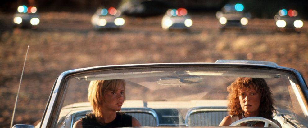 """PHOTO: Geena Davis and Susan Sarandon sitting in their convertible with squad cars behind them in a scene from the film """"Thelma & Louise"""" in 1991."""