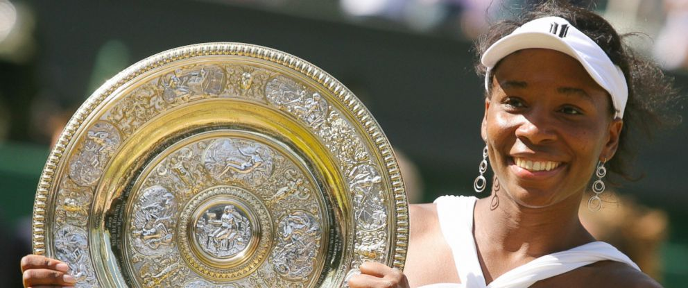 PHOTO: US Venus Williams poses holding her trophy after beating her sister Serena during their final tennis match of the 2008 Wimbledon championships at The All England Tennis Club in southwest London, July 5, 2008. Venus Williams won 7-5, 6-4.