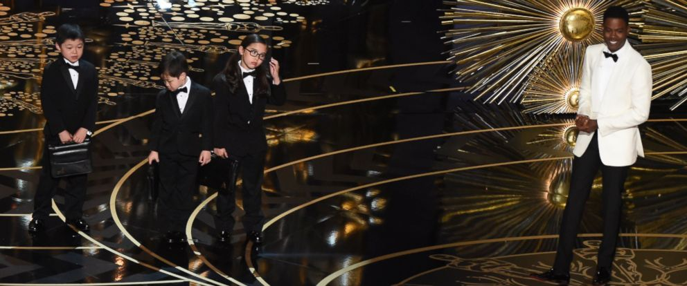 PHOTO: Chris Rock presents children representing accountants from PricewaterhouseCoopers on stage at the 88th Oscars, Feb. 28, 2016 in Hollywood, Calif.