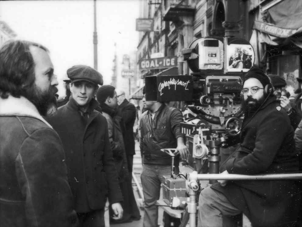 PHOTO: American director Francis Ford Coppola sitting with the camera on the set of his film The Godfather; Part II, 1974. Robert DeNiro is standing at left.