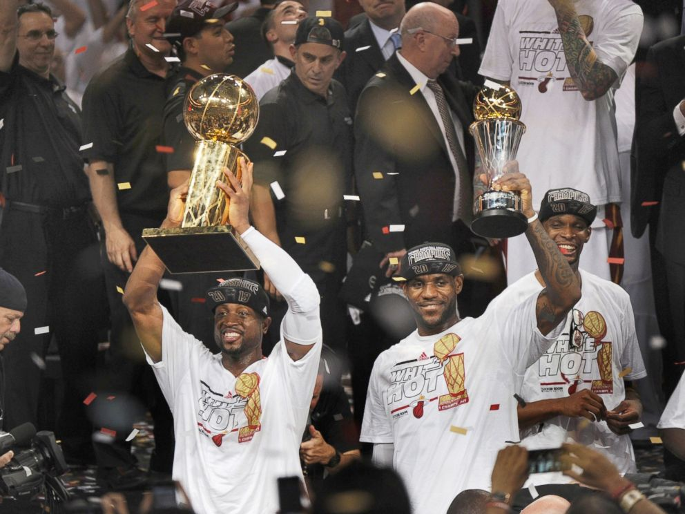 PHOTO: With trophies in hand, the Miami Heats LeBron James and Dwyane Wade celebrate after a 95-88 win against the San Antonio Spurs in Game 7 of the NBA Finals in Miami, June 20, 2013.