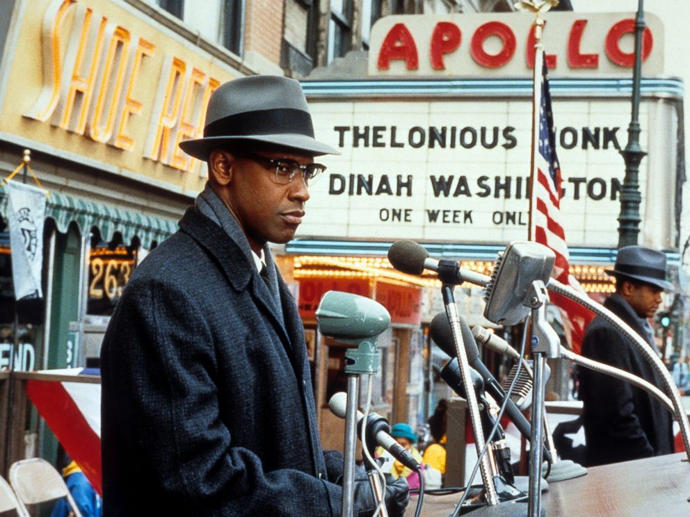 PHOTO: Denzel Washington standing behind microphones in a scene from the film Malcom X, 1992.