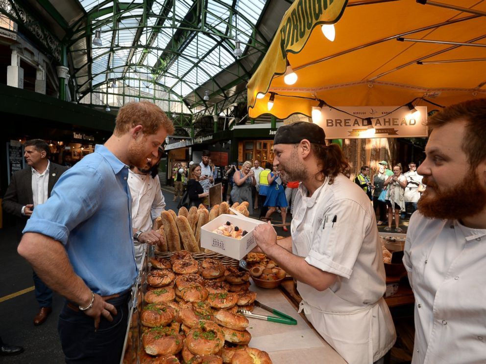 PHOTO: Prince Harry buys doughnuts from Bread Ahead stall during a visit to Borough Market in London, which has opened yesterday for the first time since the London Bridge terrorist attack, June 15, 2017.