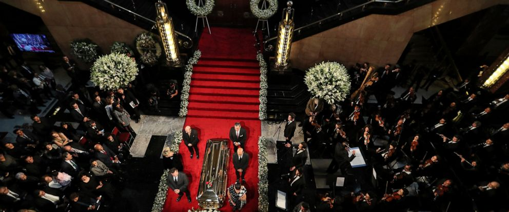People stand next to the casket containing the remains of Mexican crooner Jose Jose during a homage at the Palace of Fine Arts in Mexico City, Wednesday, Oct. 9, 2019. Jose Jose died Sept. 28 in South Florida. His body was cremated in Miami and it wa