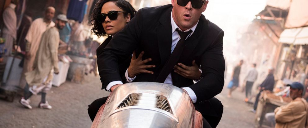 "This image released by Sony Pictures shows Chris Hemsworth, foreground, and Tessa Thompson in a scene from Columbia Pictures ""Men in Black: International."" (Giles Keyte/Sony/Columbia Pictures via AP)"