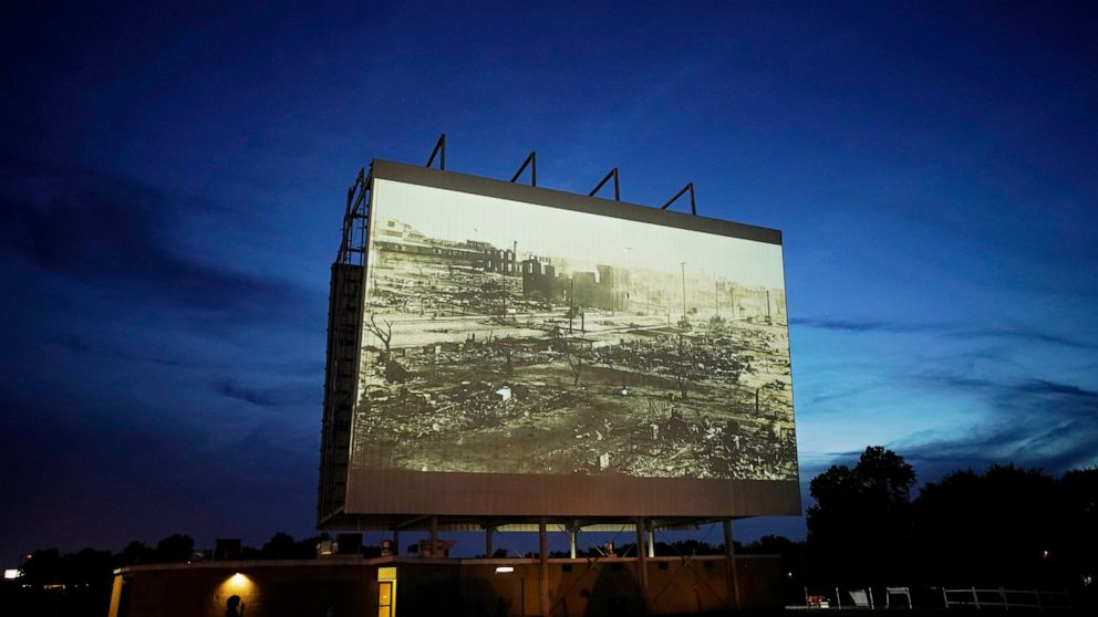 """FILE - In this Wednesday, May 26, 2021 file photo, an image of devastation from the Tulsa Race Massacre is shown on a drive-in movie screen from the documentary """"Rebuilding Black Wall Street,"""" during a screening of documentaries for centennial commem"""