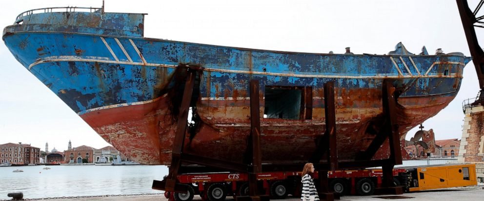 A woman walks past the wreck of the Barca Nostra fishing boat, which sank in the Mediterranean Sea in 2015 with 700 migrants on board, is displayed at the 58th Biennale of Arts exhibition in Venice, Italy, Tuesday, May 7, 2019. The wreck is part of