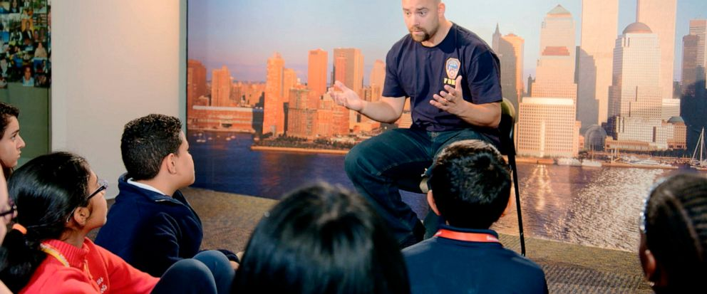 """This image released by HBO shows a New York City Fireman speaking to children in a scene from the documentary """"What Happened on September 11,"""" a short film aimed at young people to explain to them what happened on Sept. 11, 2001. The program debuts o"""