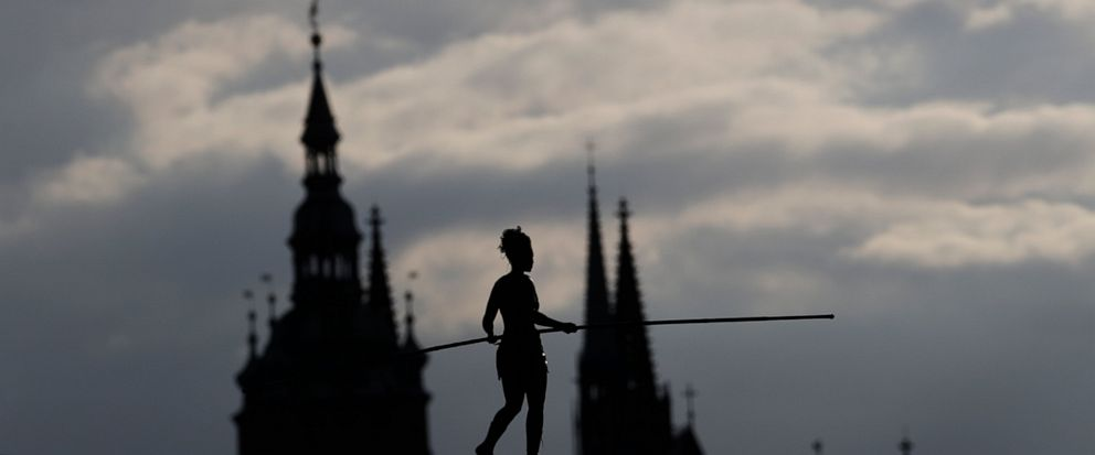 French tightrope walker Tatiana-Mosio Bongoga balances over the Vltava river during her performance to open an international new circus festival in Prague, Czech Republic, Wednesday, Aug. 14, 2019. The Prague Castle is in the background. (AP Photo/Pe