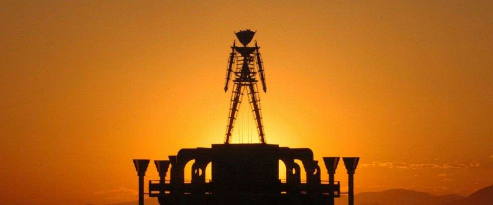 """FILE - In this Sept. 2, 2006 file photo, """"The Man,"""" a stick figured symbol of the Burning Man art festival, is silhouetted against a morning sunrise in Nevadas Black Rock Desert. The U.S. Bureau of Land Management is recommending attendance be cappe"""