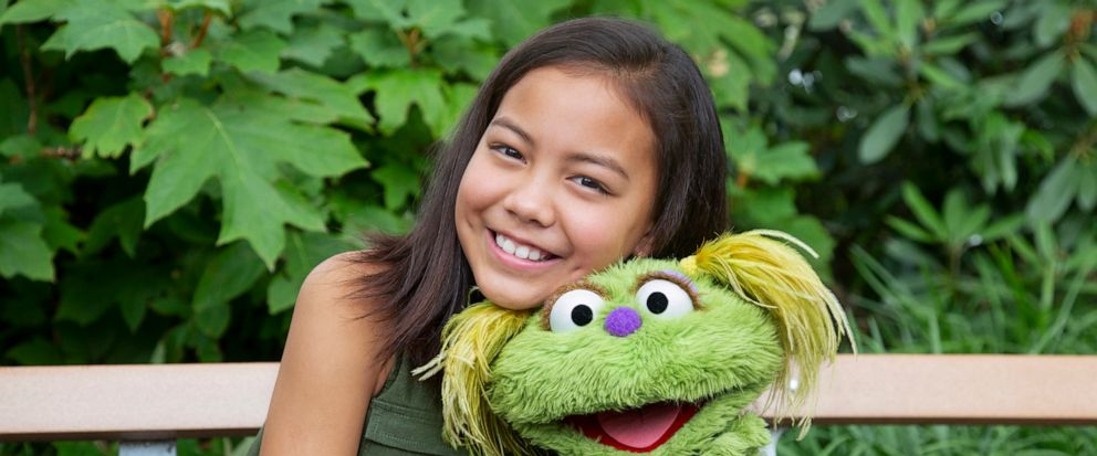 """This undated image released by Sesame Workshop shows 10-year-old Salia Woodbury, whose parents are in recovery, with """"Sesame Street"""" character Karli. Sesame Workshop is addressing the issue of addiction. Data shows 5.7 million children under 11 live"""