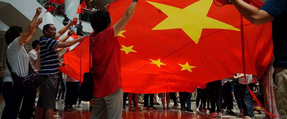 Pro-China protesters wave a Chinese national flag at a shopping mall in Hong Kong, Friday, Sept. 13, 2019. Protest-related activities are expected to continue Friday, when Chinese celebrate the Mid-Autumn Festival with lanterns and mooncakes. Police