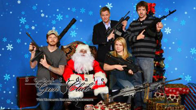 """PHOTO: ABCs David Wright (back left) and producer Erin Keohane (front) hold AK-47s while posing with Santa for the Scottsdale Gun Clubs """"Santa and Machine Guns"""" event."""