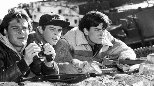 PHOTO: After hiding in the mountains for a month, Jed (Patrick Swayze, left), Robert (C. Thomas Howell, center) and Matt (Charlie Sheen, right) secretly observe enemy movements before venturing back into their occupied hometown in Red Dawn, 1987.